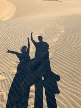 Shapes of two people and footprints on the sand, Maspalomas Gran Canaria Фото со стока - 135987751