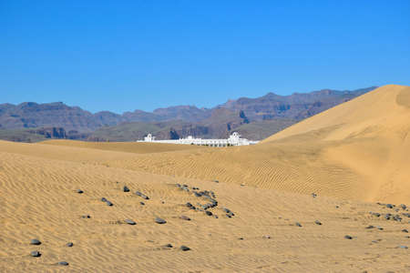 Dunes of Maspalomas with the building and mountains in the background, Gran Canaria Spain Фото со стока