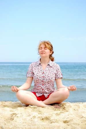 meditating women on the beach, sea, sky photo
