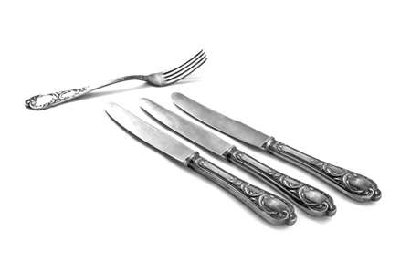 three table knifes and fork on white background photo