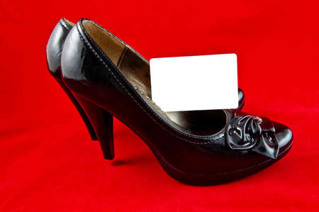 black female shoes with white card on red background  photo