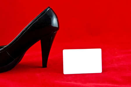 black female one shoe with white card on red background  photo