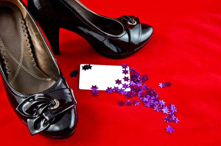 black female shoes with white card and violet stars on red background  photo
