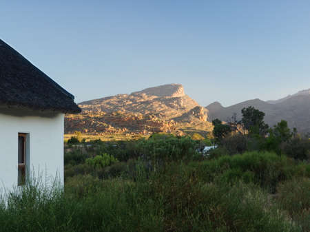Tiny house in the backcountry at sunset in South Africa with rocky mountain illuminated