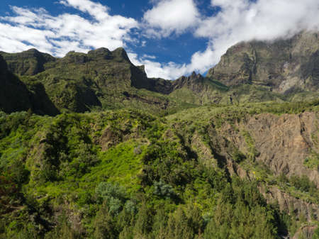 Mafate Cirque outlook in Reunion Island with dense vegetation and partially cloudy sky