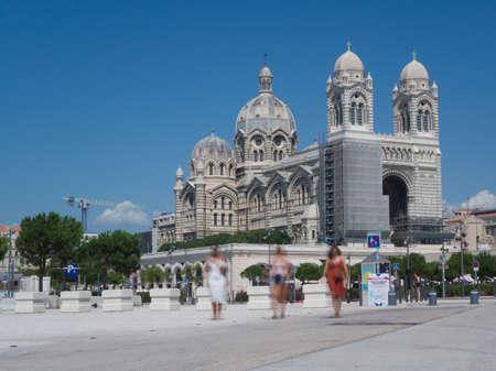 View on the impressive renovated cathedral in Marseille, discovering the old architecture with three blurred walking women Stock Photo