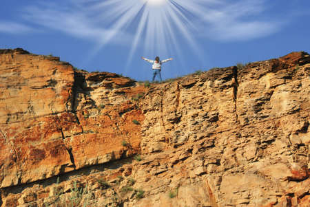 The woman at top of a rock in beams of the sun (symbolizing freedom) photo