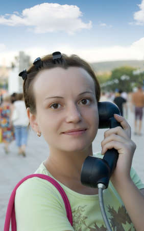 speaking tube: The girl with a telephone tube. The girl speaking on a call box in the street