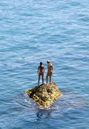voyeur: Two girls on a rock in the middle of picturesque ocean