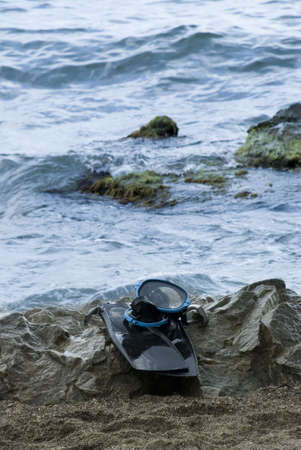 Accessories to diving. A mask, flippers, a snorkel on coast of ocean Stock Photo - 1755332