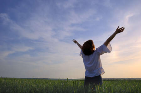 Concept - freedom. The girl photographed behind on a background of a sunset above a wheaten field photo