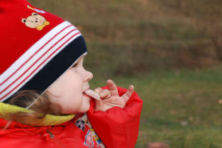 The little girl eating sausage (ham) on the nature Stock Photo - 1755122
