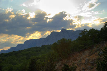 gleams: The sky and mountains. Gleams of the sun through dense overcast above mountains
