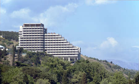 Modern hotel on a slope of picturesque mountain. With greater mountains on a background and the effective sky photo