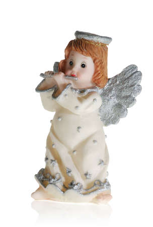 godlike: Toy - an angel playing on a flute. It is isolated on a white background