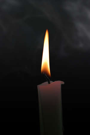 easter candle is burning: candle with smoke on the isolated black background
