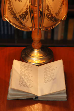 The book of verses under light of a desk lamp. A cosy atmosphere Stock Photo - 2498506
