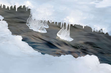 The winter river. An ice-hole in the frozen river with a rough stream Stock Photo - 2529663