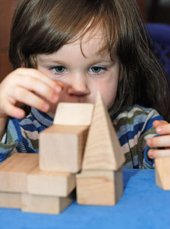 The child - architect. The girl collecting a design from wooden cubes. Stock Photo - 2725268