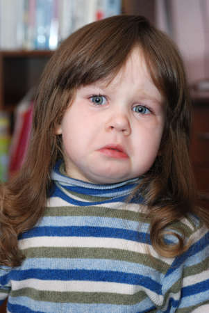 The crying child. disconcerted the girl - 2 years photo