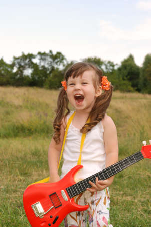 The girl with a guitar. The three-year child with a musical instrument Stock Photo