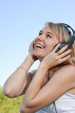 The girl in headphones. The young woman listening music through headphones Stock Photo - 3412636