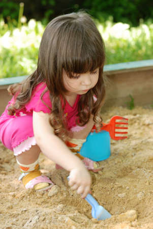 the sandbox: The girl playing to a sandbox. Caucasian the child, park of rest Stock Photo