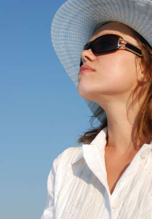 afflatus: The woman in glasses and a hat on a background of the sky. The adult girl in white clothes
