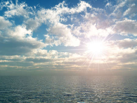 flare up: The bright sun above ocean. Soft fluffy clouds Stock Photo
