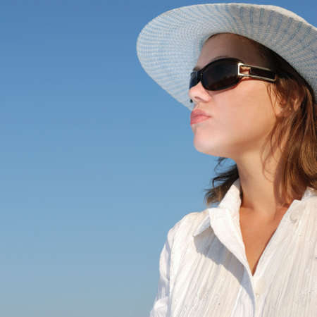 The woman in glasses and a hat on a  of the sky. The adult girl in white clothes photo