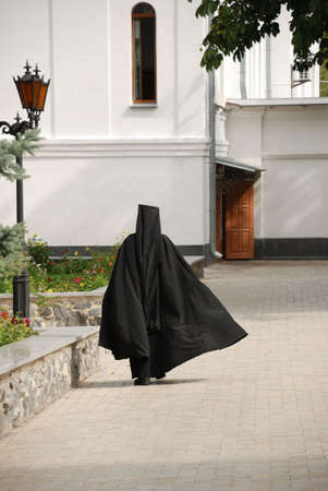 The running monk. The man in a cassock - the novice of a mans monastery photo