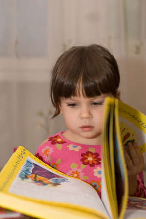 grasping: The child reading the book. The three-year girl in  conditions