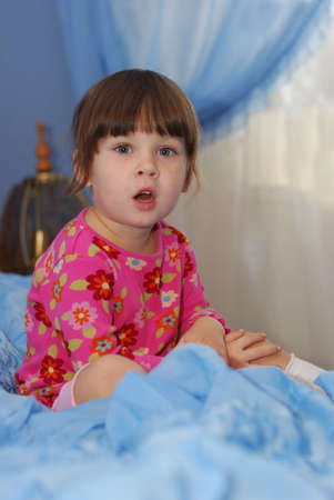 expressing: The little girl on a bed. The three-year child of the European nationality Stock Photo