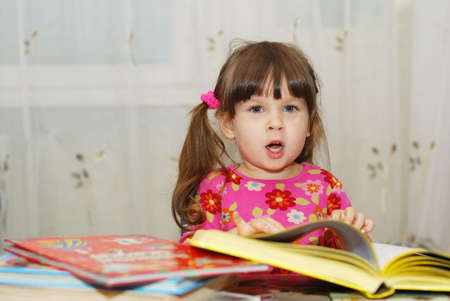 grasping: The child reading the book. The three-year girl in house conditions