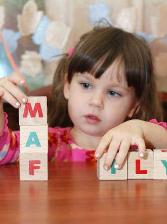 La ni�a y cubos de juguete. El ni�o se percibe una familia de palabras a partir de cubos. Foto de archivo - 3802568