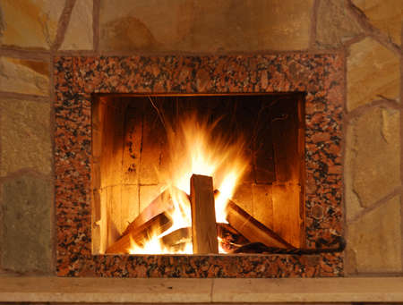 mantelpiece: Fireplace. Flaring fire in a fireplace the reveted wild stone and a marble