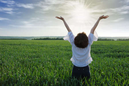 The girl on a field. The woman with the lifted hands to the sky on a green meadow Stock Photo