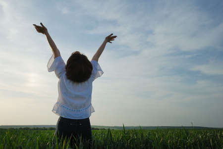 arms outstretched: The girl on a field. The woman with the lifted hands to the sky on a green meadow Stock Photo