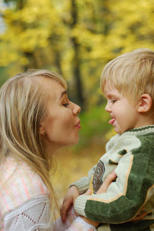 Mother with the child. On a background of yellow autumn foliage photo