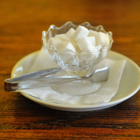 pinchers: Sugar. The refined pieces of sugar in a glass Stock Photo