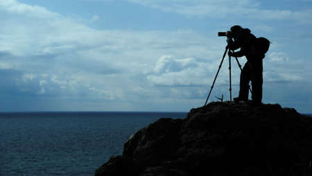 The photographer on mountain. A silhouette of the person with the camera on a background of the sky photo