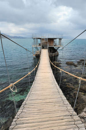 hinged: The hinged bridge. Above the sea to island on which it is located by cafe