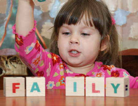 The girl and toy cubes. The child collecting a word family from cubes. photo