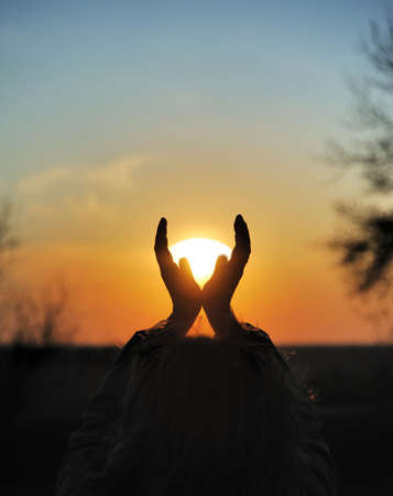 Decline in hands. A sunset on a background of the lifted female hands Stock Photo - 4728320