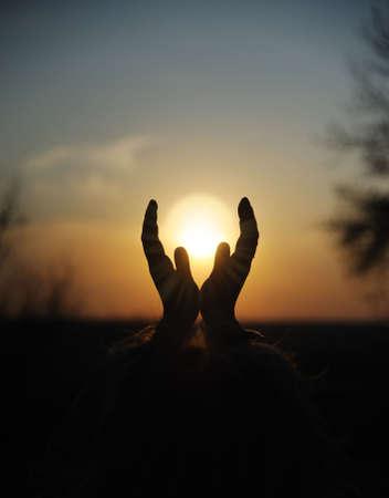 inspiratie: Daling in handen. Een zonsondergang op de achtergrond van de opgeheven vrouwelijke handen Stockfoto