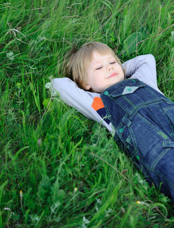 The boy on a green grass. The weakened condition of the small child Stock Photo