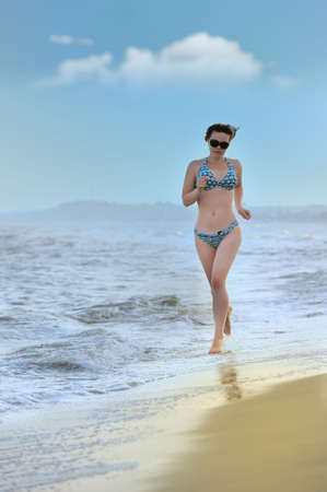 The girl running on seacoast. The European appearance in sunglasses photo