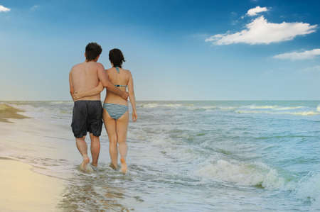 Pair on seacoast. The enamoured guy and the girl walking on coast Stock Photo - 5162719
