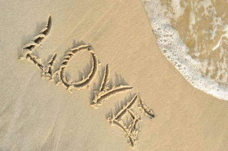 Inscription love on sand. Sea coast with a rolling wave on an inscription photo