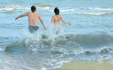 Pair on seacoast. The enamoured guy and the girl walking on coast Stock Photo - 5167247